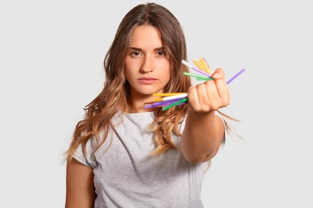 Atractiva mujer seria sostiene crujientes pajitas de plástico en la mano, demuestra su fuerte sensación de vivir en un planeta limpio