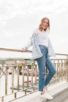 Atractiva mujer sonriente apoyada en la barandilla del puente y escuchando música.