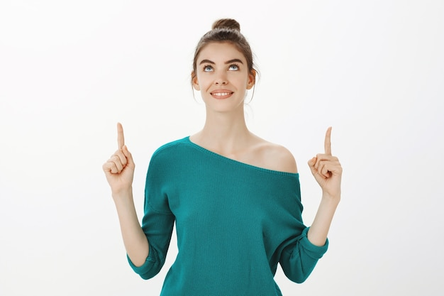 Atractiva mujer sonriente apuntando con el dedo hacia arriba, leyendo el anuncio o viendo su logotipo