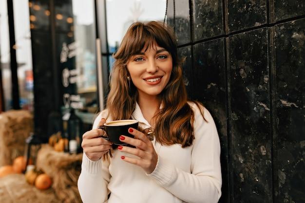 Atractiva mujer sonriente con cabello castaño ondulado disfrutando de un café afuera