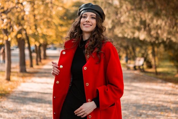 Atractiva mujer sonriente con estilo con el pelo rizado caminando en el parque vestida con abrigo rojo cálido otoño moda moda, estilo callejero, con sombrero de boina