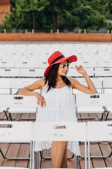 Atractiva mujer sonriente feliz vestida con vestido blanco, sombrero rojo, gafas de sol sentado en el teatro al aire libre de verano en silla sola, tendencia de moda de estilo callejero de primavera