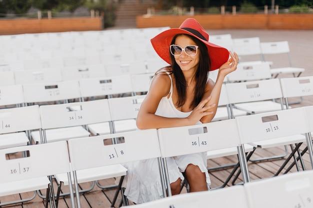 Atractiva mujer sonriente feliz vestida con vestido blanco, sombrero rojo, gafas de sol sentado en el teatro al aire libre de verano solo, muchas sillas, tendencia de moda de estilo callejero de primavera, saludando con la mano hola