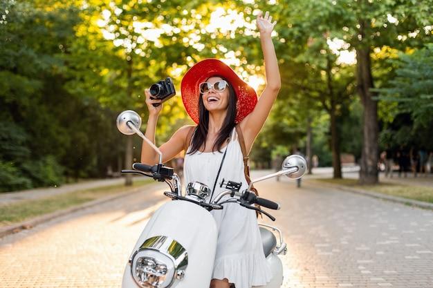 Atractiva mujer sonriente montando en moto en la calle en traje de estilo veraniego con vestido blanco y sombrero rojo viajando de vacaciones, tomando fotos en la cámara de fotos vintage, saludando con la mano, saludo