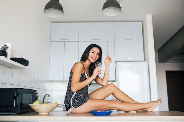 Atractiva mujer sonriente en pijama desayunando en la cocina por la mañana, comiendo galletas y bebiendo leche, estilo de vida saludable, piernas largas y delgadas