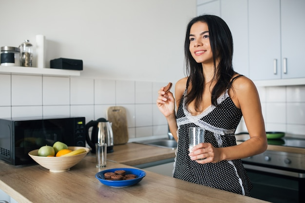 Atractiva mujer sonriente en pijama desayunando en la cocina por la mañana, comiendo galletas y bebiendo leche, estilo de vida saludable