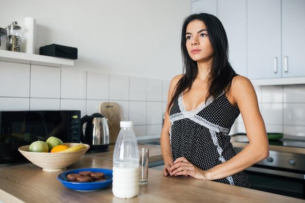 Atractiva mujer sonriente en pijama desayunando en la cocina por la mañana, en la mesa con galletas y leche, estilo de vida saludable