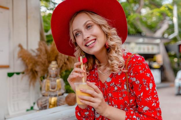 Atractiva mujer sonriente rubia elegante con sombrero rojo de paja y blusa traje de moda de verano bebiendo batido de cóctel de frutas naturales