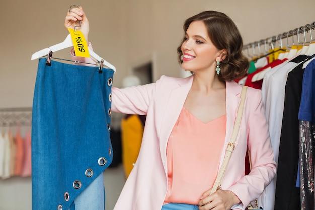 Atractiva mujer sonriente sosteniendo falda de mezclilla en percha en tienda de ropa