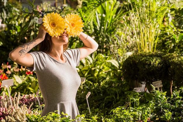 Atractiva mujer sonriente sosteniendo flores cerca de los ojos
