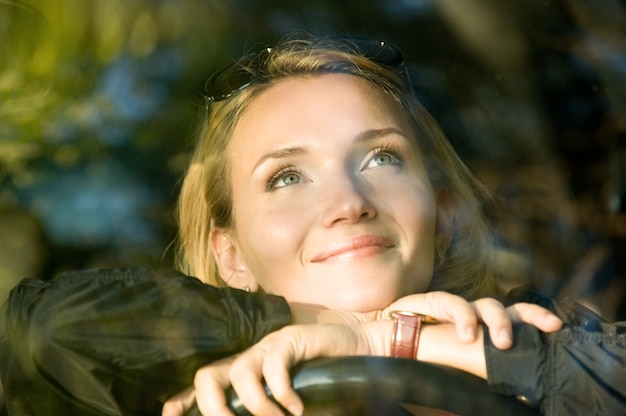 Atractiva mujer sonriente sueña en el coche nuevo y mirando hacia arriba - al aire libre
