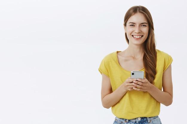 Atractiva mujer sonriente mediante teléfono móvil, mensaje de texto en la aplicación o red social