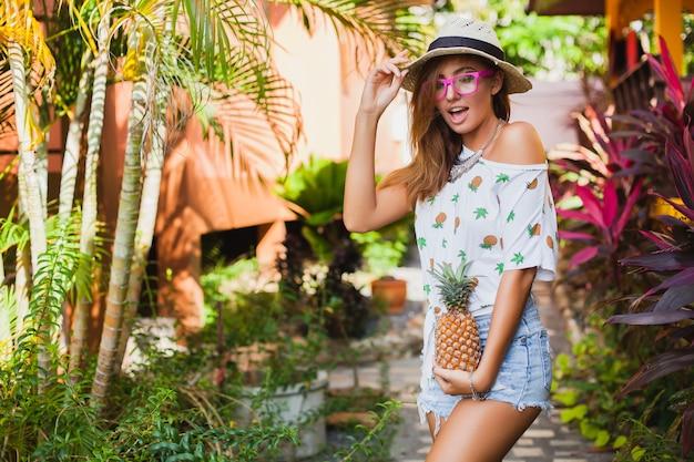 Atractiva mujer sonriente de vacaciones en camiseta impresa sombrero de paja moda de verano, manos sosteniendo piña