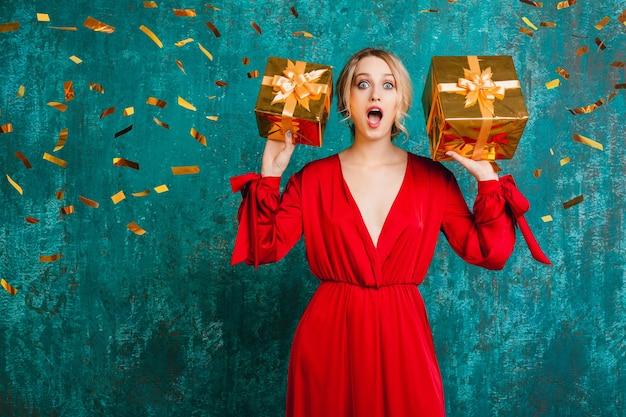Atractiva mujer sorprendida en elegante vestido rojo celebrando la navidad y el año nuevo con regalos