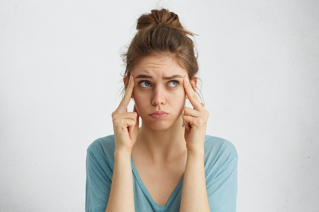 Atractiva mujer sosteniendo los dedos en las sienes
