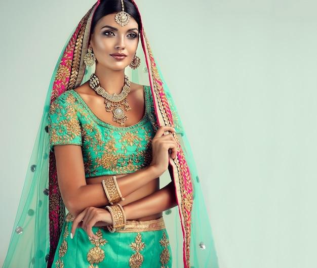 Atractiva mujer vestida con traje indio sari y chal dupatta con borde dorado y elegante conjunto de joyas