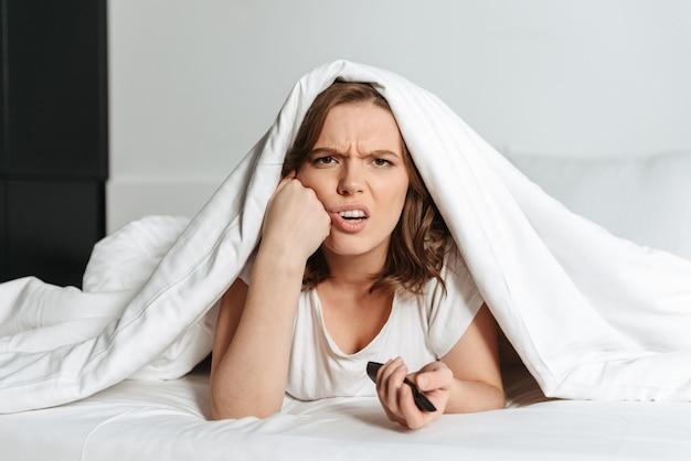 Atractiva mujer yupset oung acostado en la cama en casa viendo la televisión