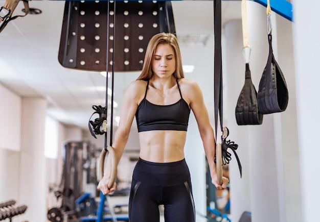 Atractiva, musculosa, joven en ropa deportiva negra, entrena en los anillos en el gimnasio.