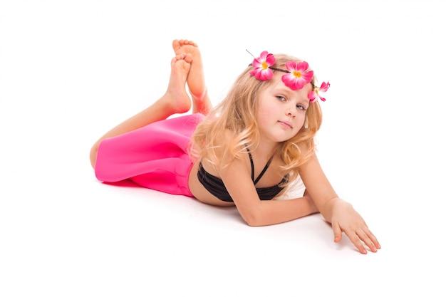 Atractiva niña en bikini negro, falda rosa y corona rosa, se encuentra.