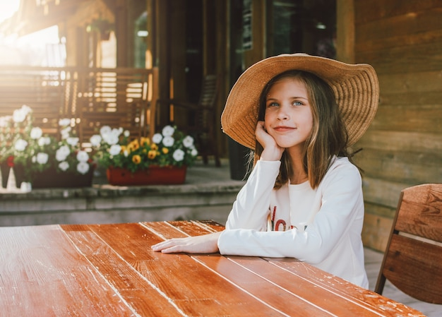 Atractiva niña preadolescente en sombrero de paja con ojos azules sentado y soñando en la mesa en el patio de la cabaña de madera