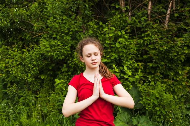 Atractiva niña rezando con los ojos cerrados en la naturaleza