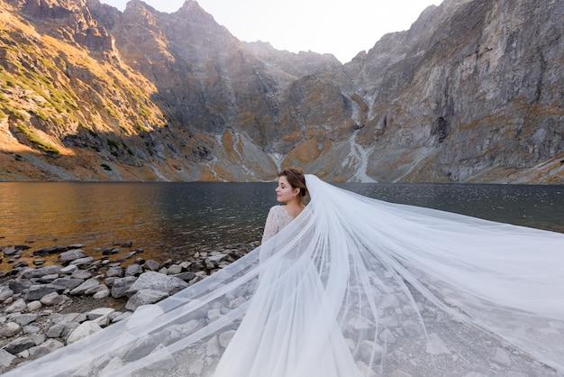 Atractiva novia con los ojos cerrados y velo ondulado está de pie frente al lago rodeado de montañas de otoño en el día soleado