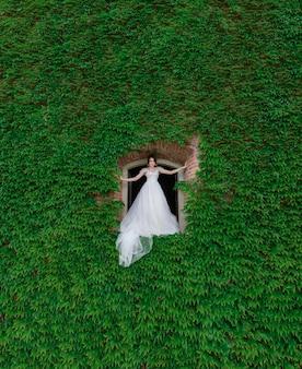 Atractiva novia está de pie en el agujero hecho en la pared cubierta de hojas verdes