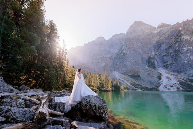 Atractiva novia está de pie sobre la roca con una vista impresionante del lago highland con agua de color verde en el día soleado, las montañas tatry