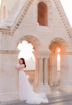 Atractiva novia en tierno vestido de moda está de pie cerca de la columna de piedra en un cálido día de verano