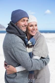Atractiva pareja abrazándose en la playa en ropa de abrigo
