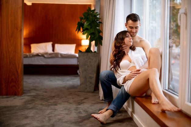 Atractiva pareja amorosa sentada en el alféizar de la ventana de la habitación