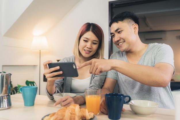Atractiva pareja asiática joven distraída en la mesa con periódico y teléfono celular