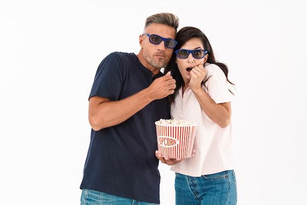 Atractiva pareja asustada vistiendo ropa casual que se encuentran aisladas sobre una pared blanca, viendo una película con palomitas de maíz y gafas 3d