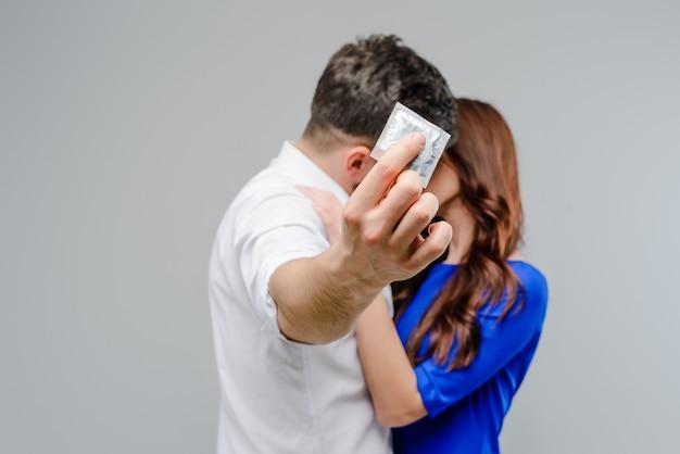 Atractiva pareja besándose con un condón en foco aislado sobre fondo gris
