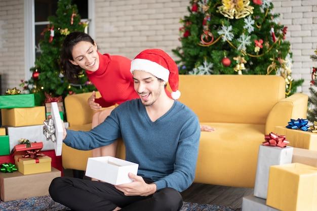 Atractiva pareja caucásica de amor está celebrando la navidad en casa