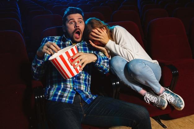 Atractiva pareja caucásica joven viendo una película en una sala de cine, una casa o un cine. luce expresivo, asombrado y emocionado. sentarse solo y divertirse. relación, amor, familia, fin de semana.