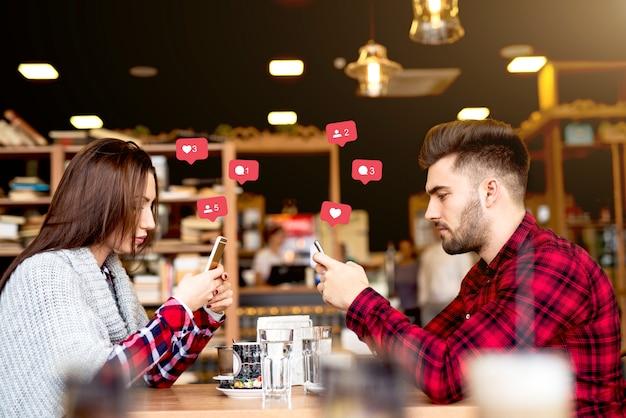Atractiva pareja caucásica vestido casual usando teléfonos inteligentes para las redes sociales mientras estaba sentado en la cafetería