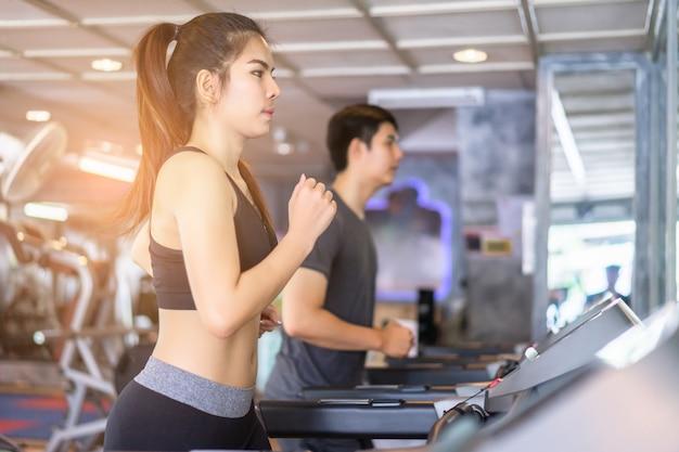 Atractiva pareja corriendo en la caminadora en el gimnasio. trabajando juntos