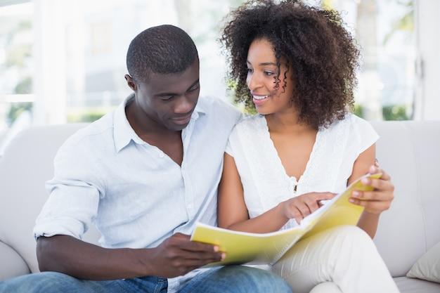 Atractiva pareja descansando juntos en el sofá mirando el álbum de fotos en casa en la sala de estar