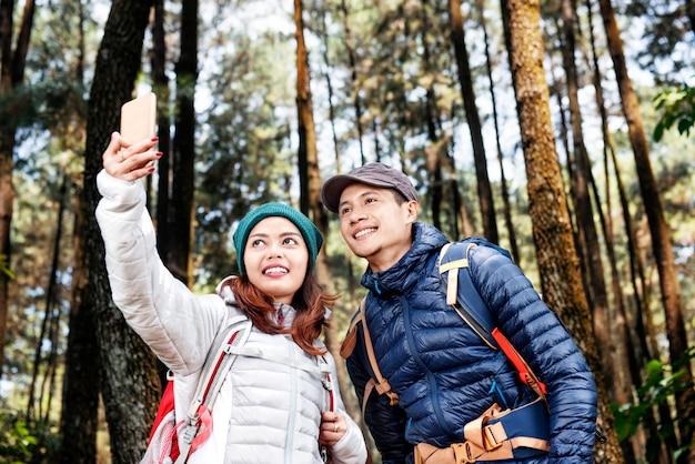 Atractiva pareja de excursionistas asiáticos tomando foto selfie con teléfono móvil