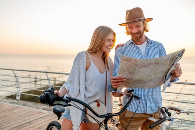Atractiva pareja feliz de amigos que viajan en verano en bicicleta, hombre y mujer con cabello rubio boho hipster estilo moda divirtiéndose juntos