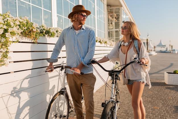 Atractiva pareja feliz de amigos que viajan en verano en bicicleta, hombre y mujer con cabello rubio