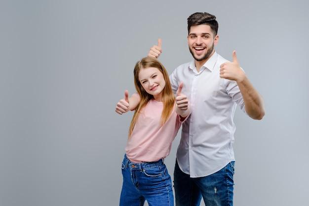 Atractiva pareja feliz muestra los pulgares arriba aislados sobre fondo gris
