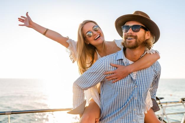 Atractiva pareja feliz riendo viajando en verano por mar