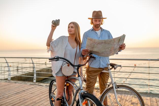 Atractiva pareja feliz viajando en verano en bicicleta, hombre y mujer con cabello rubio boho estilo hipster divirtiéndose juntos, mirando en el mapa de turismo tomando fotos en la cámara