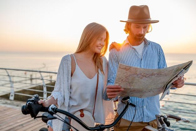 Atractiva pareja feliz viajando en verano en bicicleta, hombre y mujer con cabello rubio boho hipster estilo moda divirtiéndose juntos, mirando en el mapa de turismo