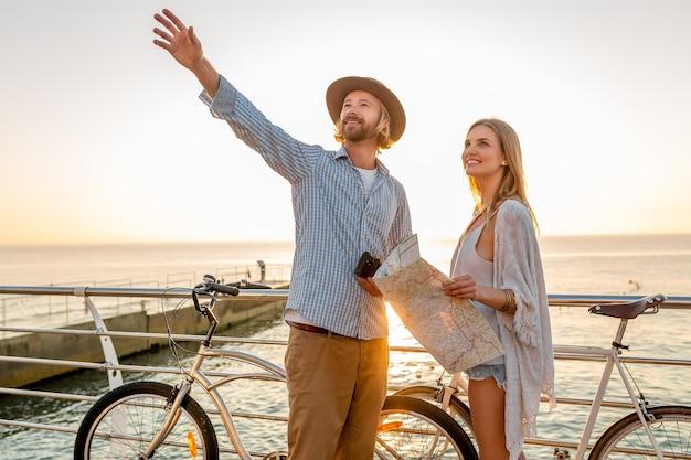 Atractiva pareja feliz viajando en verano en bicicleta, hombre y mujer con cabello rubio boho hipster estilo moda divirtiéndose juntos