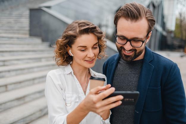 Atractiva pareja de hombre y mujer en el centro urbano de la ciudad, sosteniendo el teléfono y mirando