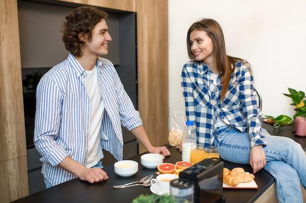 Atractiva pareja de hombre y mujer enamorados desayunando juntos en la mañana en la cocina