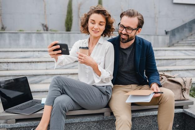 Atractiva pareja de hombre y mujer sentados en las escaleras en el centro urbano de la ciudad